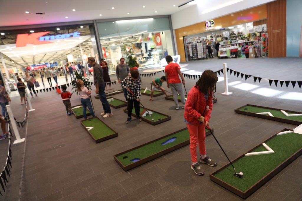 People playing Mini Golf inside a shopping centre