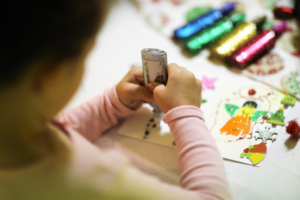 Young child using glitter glue at an arts and crafts event