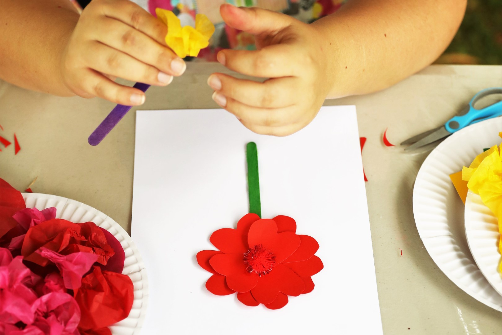 Young child making flowers at an arts and crafts event