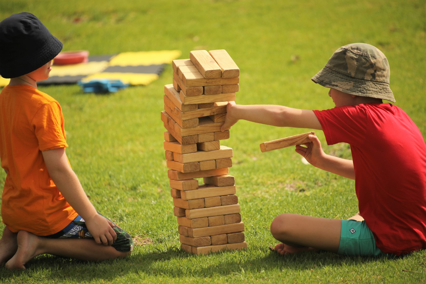 Two kids playing Jenga at an outdoors event